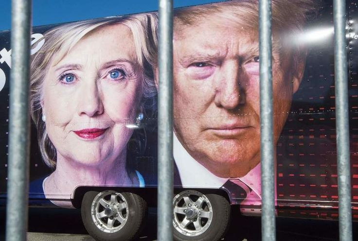 Images of Hillary Clinton and Donald Trump are seen on a CNN vehicle behind a security fence on Sept. 24, 2016, at Hofstra University in Hempsted, New York.