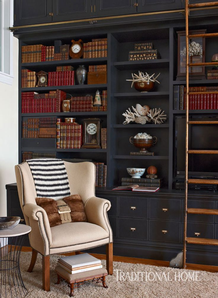 Library with black built-in bookcases – design: Rob Stuart – photo: Francesco Lagnese – Traditional Home