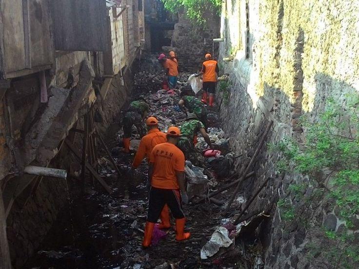 Anggota TNI bersama petugas PPSU gotong royong membersihkan sampah