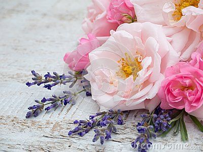 Pale and bright roses and provence lavender bouquet on the wooden rustic background
