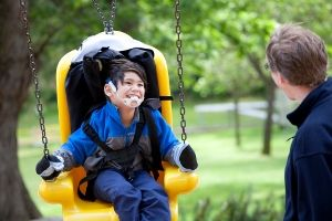 Child with cerebral palsy using swing