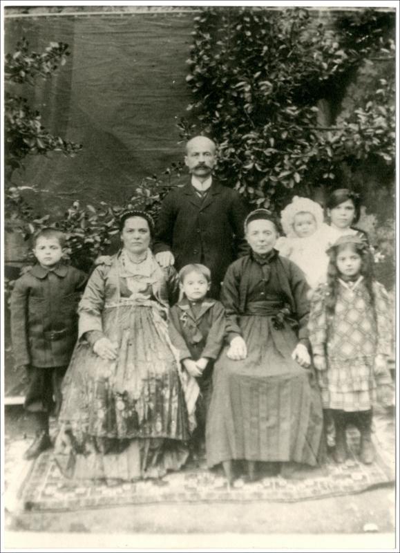 Οικογένεια από τη  Νάουσα Ημαθίας.  Ημερομηνία Έκδοσης: 6-Απριλίου-1911. Συλλογή Χρυσάνθης Κωστοπούλου: Νάουσα (Ημαθία).  Δημόσια Κεντρική Βιβλιοθήκη της Βέροιας