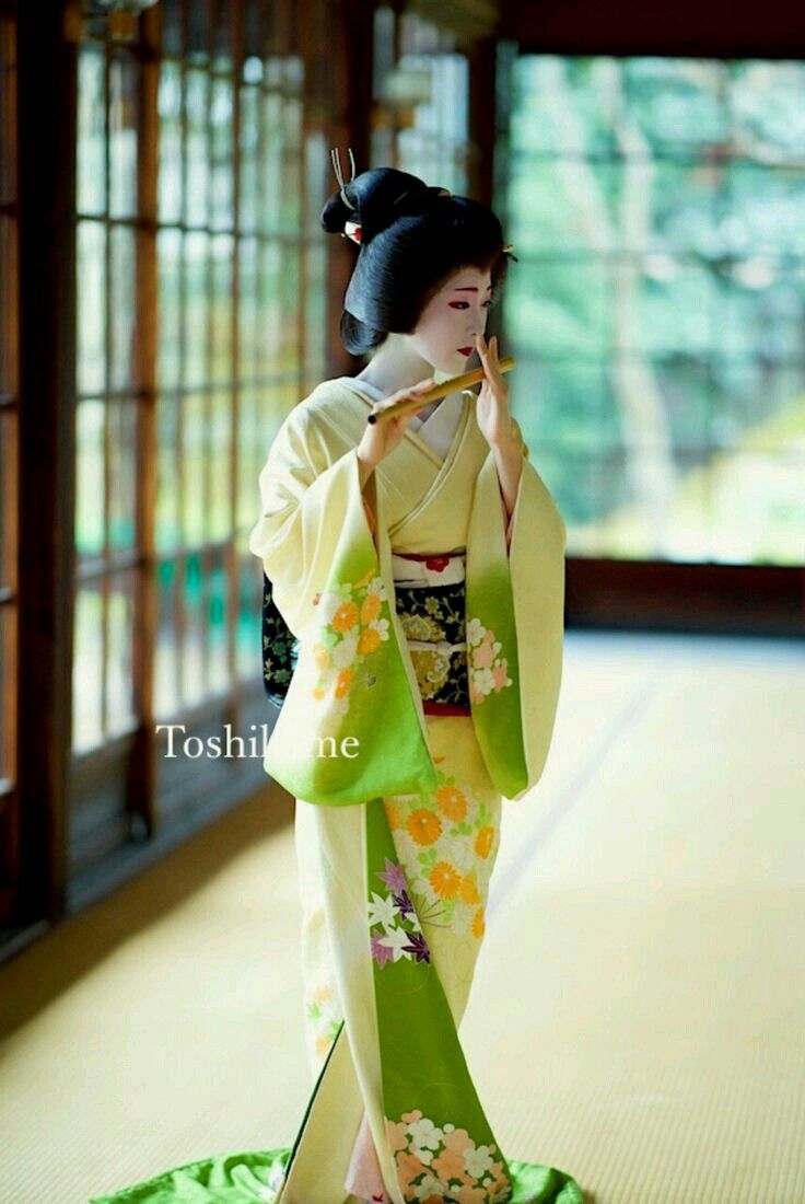 Geiko(Geisha). Kyoto. Japan. She is playing a Japanese bamboo flute.