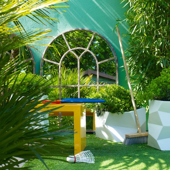 Small garden with wall mirror and yellow plastic table