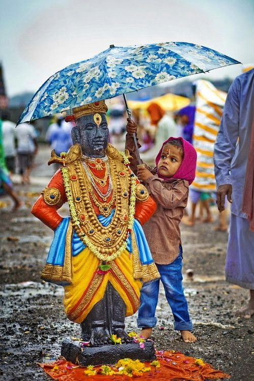 True Devotion The boy holds an umbrella for beautiful idol of God Vitthal