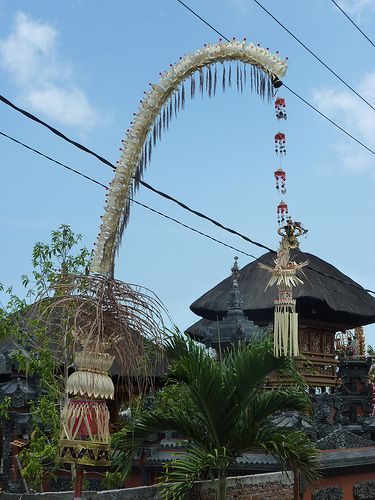 A Hindu 'penjor' outside a temple in Balangan, Bali. The penjor is a tall, curved bamboo pole decorated with coconut leaves with an offering at the base. This is one of the media used by Hindus in Bali as part of almost every important ceremony, especially for the anniversary temple celebrations.