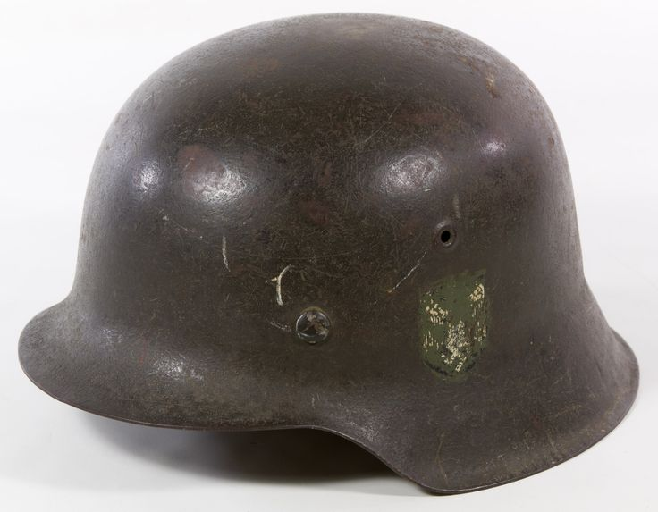 Lot 207: World War II German Nazi M42 Helmet; Having a metal shell, a brown leather sweat band mounted onto a metal ring and a subdued (intentionally obscured) eagle with swastika emblem on the side of the exterior