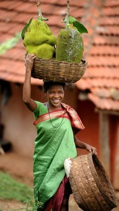 Jack fruit vendor wearing a smile and a lovely green sari