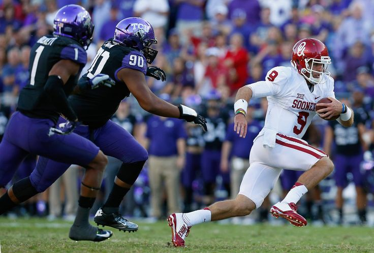 Quarterback Trevor Knight #9 of the Oklahoma Sooners carries the ball against safety Chris Hackett #1 of the TCU Horned Frogs and defensive tackle Terrell Lathan #90 of the TCU Horned Frogs in the second half at Amon G. Carter Stadium on October 4, 2014 in Fort Worth, Texas.