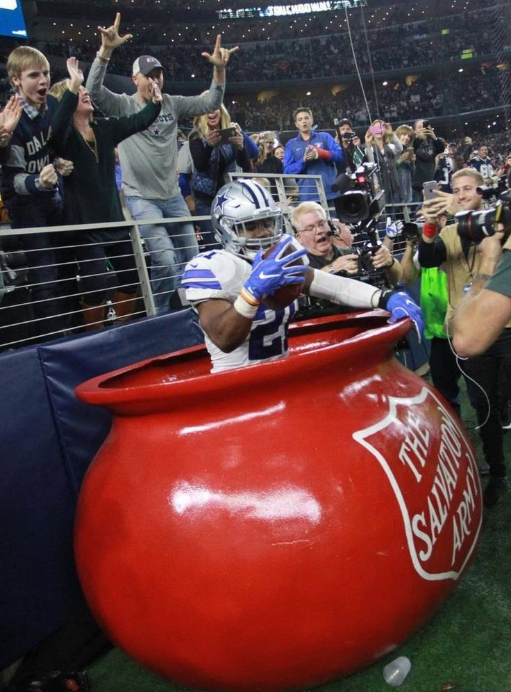 Dallas Cowboys running back Ezekiel Elliott jumped into the Salvation Army red kettle after scoring a second-quarter touchdown against the Tampa Bay Buccaneers on Sunday at AT&T Stadium in Arlington, Texas .#KettleHop goes viral