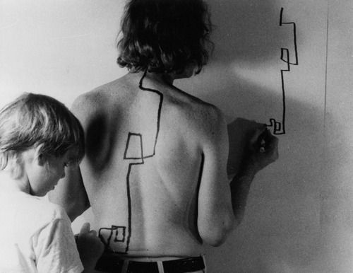 "Dennis Oppenheim - Two-stage Transfer Drawing (1971)  ""As I run a marker along Eric's back he attempts to duplicate the movement on the wall. My activity stimulates a kinetic response from his sensory system. I am, therefore, drawing through him"""
