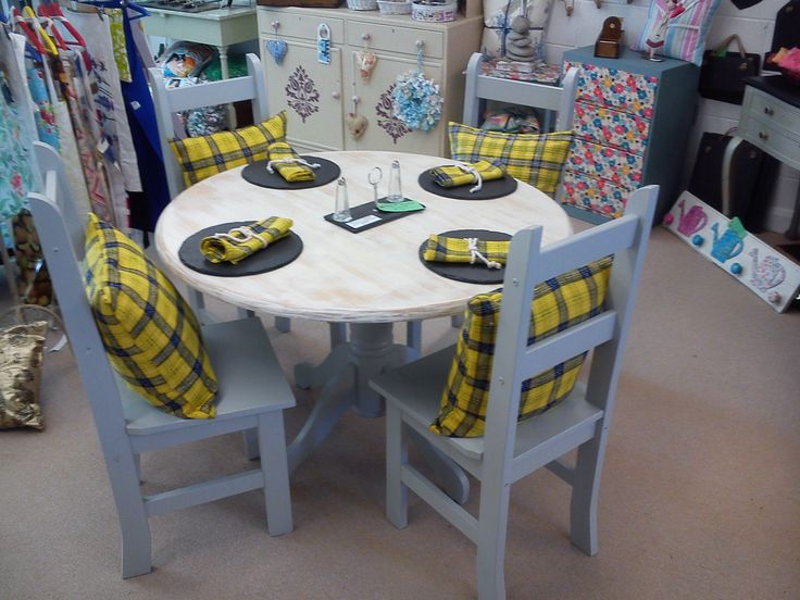 Grey, white and yellow table and chairs. With Cornish tartan effect cushions and matching serviettes. Table top has a driftwood/scrubbed effect.