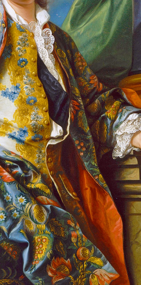 """Detail of """"at home"""" wear of a gentleman of means. Scarlet lined silk Banyan (dressing gown) of luxuriant foliage in rich colors, thrown over a silk knee length waistcoat richly embroidered with gold & blue thread with gold thread covered buttons. Delicate white lace flounce to shirt front & at wrist. White shirt open at throat - indication of """"undress"""". The dark blue watered silk sash is a portrait affectation proclaiming the sitter's importance. Unknown man, Carle Van Loo, France…"""