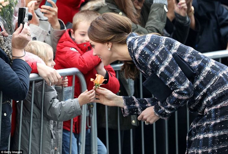 A young girl presents the delighted Duchess with a single pink rose outside The National Football Museum