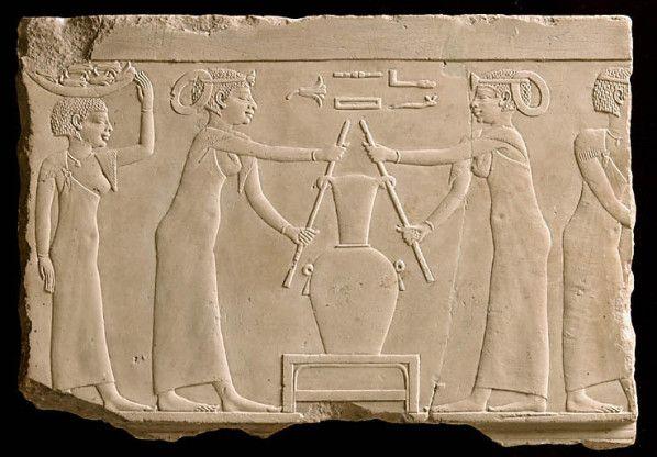"""Après vingt-quatre heures de macération, ils exprimaient à nouveau un jus par pressage, comme ci-dessus, sur ce second bas-relief provenant de la même tombe, appelé lui aussi """"Relief du lirinon"""", mais portant le numéro d'inventaire E 11162 et exposé pour sa part dans la vitrine 2 de la Salle 30, à l'étage supérieur ; puis procédaient à un deuxième ajout de cardamome broyée et d'huile aromatisée."""