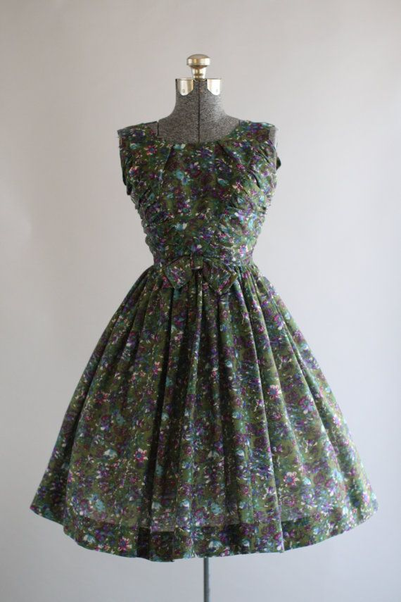 This 1950s Jerry Gilden dress features a green and purple floral print. Sleeveless. Ruching at both bodice sides. Nipped waist w/ decorative