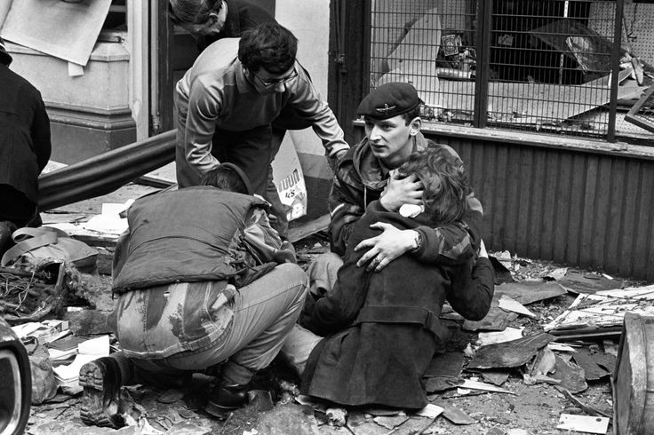 A British paratrooper takes a young girl in his arms to comfort her after she had been hurt in the bomb blast in Donegal Street, Belfast. Photos of the British Army in Northern Ireland - 1969-1979 - Flashbak