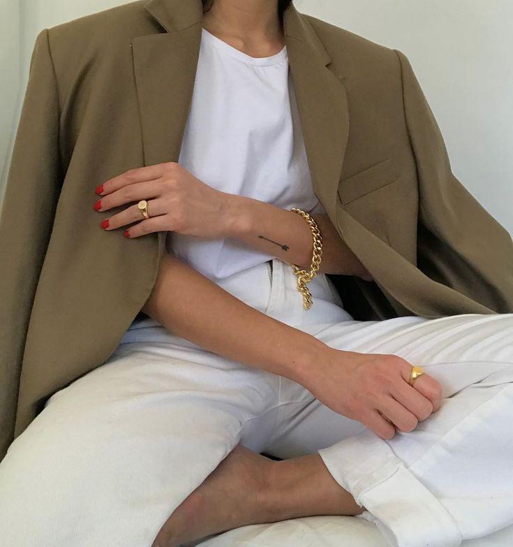 Neutral blazer, white t-shirt, signet rings, a chain bracelet, red nail polish, …