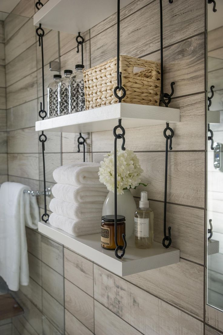 "Clever hanging storage maximizes space in the universal design bathroom. ""We had a situation where the floor and all of the walls are tiled and no place to put anything you need to have in a bathroom, so we came up with this shelving idea that David Brown built for us that is modern looking, clean, simple and it really feels perfect in this room,"" says interior designer Linda Woodrum."