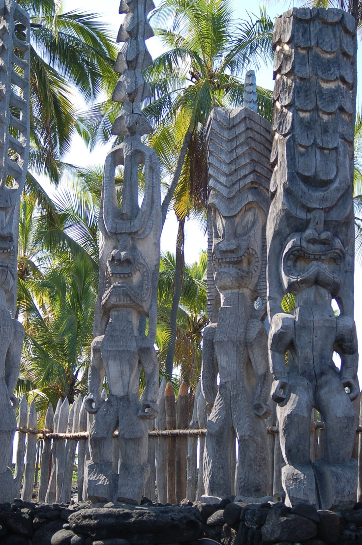 Pu'uhonua o Honaunau National Park,  Kona, Hawaii. Pictured is the Hale o Keawe, a rebuilt temple and mausoleum that once held the remains and mana of 23 noble chiefs, watched over by the giant wooden Ki'i images . This park includes the historic Royal Grounds, Great Wall and the Place of Refuge ...