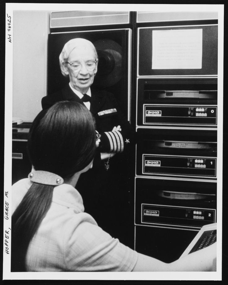 Capt. Grace Hopper, head of the Navy Programming Language Section of the Office of the Chief of Naval Operations (OP 911F), discusses a phase of her work with a staff member, August 1976. Photographed by PH2 David C. MacLean. Note DECpack computer equipment at the right. Official U.S. Navy photograph from the collections of the Naval History and Heritage Command.
