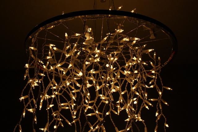 Cover metal bicycle wheel with white Christmas lights. Hang overhead.