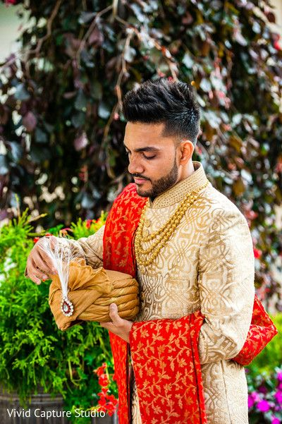 Indian groom ready in his cream and gold sherwani.