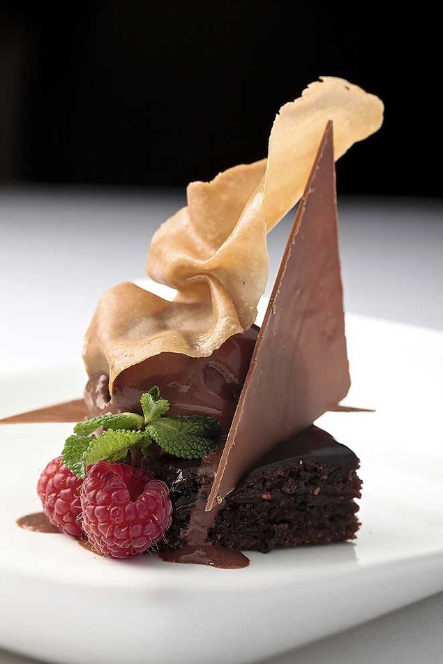 Chocolate brownie square with triangular choc garnish mint leaf raspberries and tuile/ phyllo pastry; add some chantilly/ ice cream? #catering #entertaing #crowds