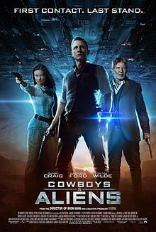 """A man wearing a metal bracelet glowing a blue light on his left wrist, with a revolver in his right hand. To the left, a woman aiming a revolver. To the right, an older man wielding a revolver. In the background, a large metal object over a desert landscape. Above is shown """"FIRST CONTACT. LAST STAND."""" Below them are the names of Daniel Craig, Harrison Ford, and Olivia Wilde above the title """"COWBOYS & ALIENS"""", film credits, and theatrical release date."""