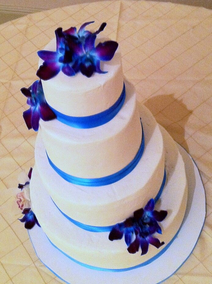 Four Tier Wedding Cake In White With Topaz Blue Ribbon Accents And Deep Purple Orchids