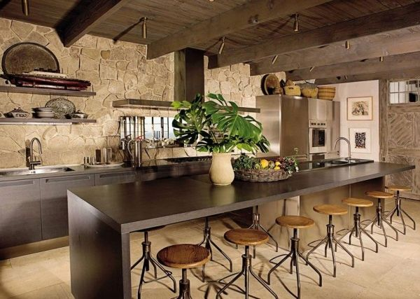 a stone wall ceiling beams and a barn door add rustic touches to the otherwise contemporary kitchen - Rustic Modern Decor