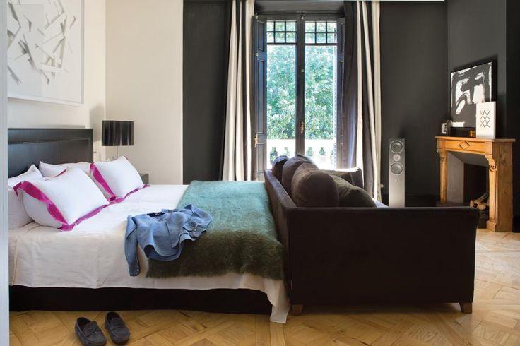 Una casona de época en contraste con su deco contemporánea  La habitación principal se conecta con el vestidor a través de un pasillo con un kilim turco en algodón y lana. Cuadro de Eduard Arbós y cabecera tapizada en cuero, diseño del dueño de casa. Ropa de cama blanca y manta de 'Ezcaray' (A Casa Bianca). A los pies, un sofá (Flexform)