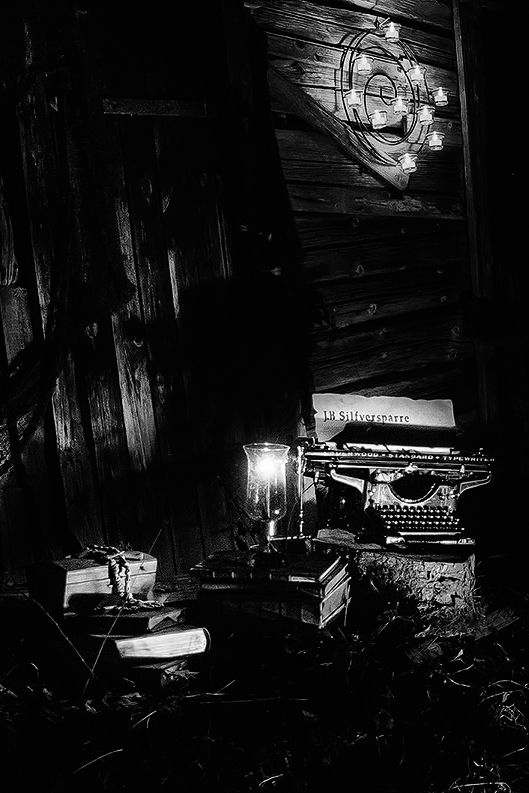Höstbild på J.B Silfversparres kontor nattetid vid ett öde skjul ute i skogen med hans skrivmaskin, böcker, skrin och lyktor. (Fantasy, Typewriter, Forest, Writer, Light, Shed, Night)