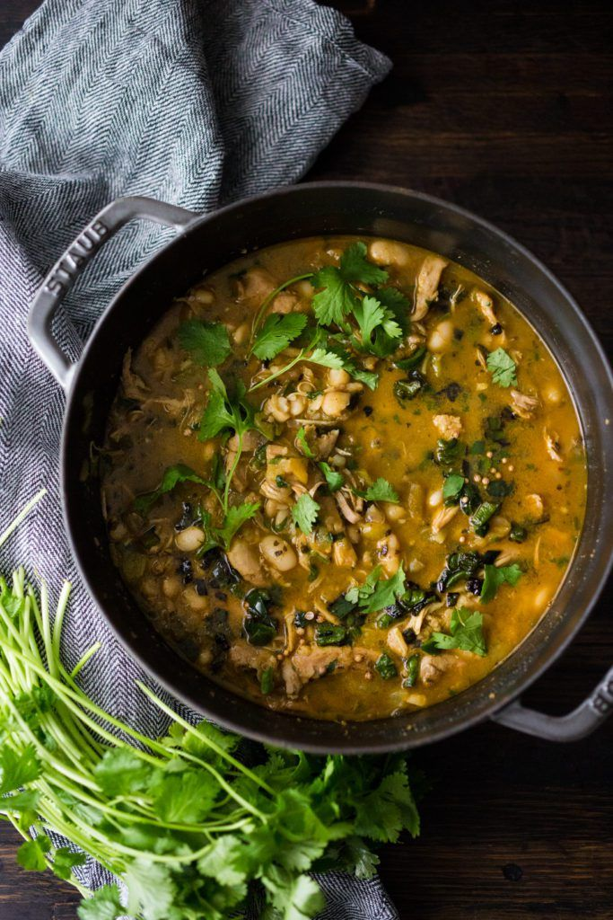 Chicken Chili Verde with white beans, poblano chilies, cilantro, coriander and lime. Tangy, spicy, this one-pot meal is hearty and delicious! | www.feastingathome.com