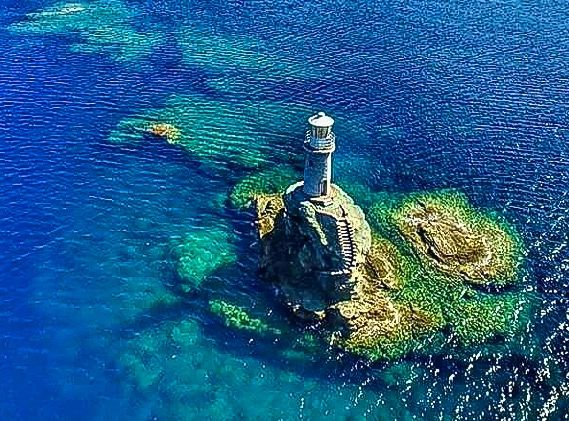 the trademark of andros island... the unique lighthouse build on a small rock at andros hora