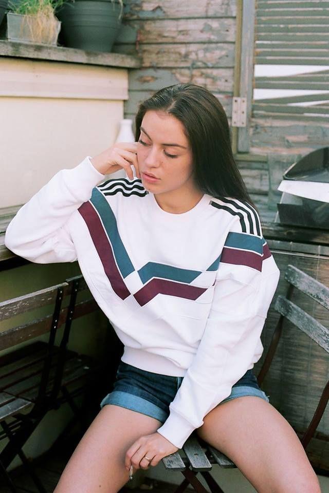 White sweatshirt w/ aqua & burgundy altered-chevrons print plus black shoulder stripes, pink lips, long charcoal hair, cuffed blue denim cutoffs; distressed wood décor, potted plants