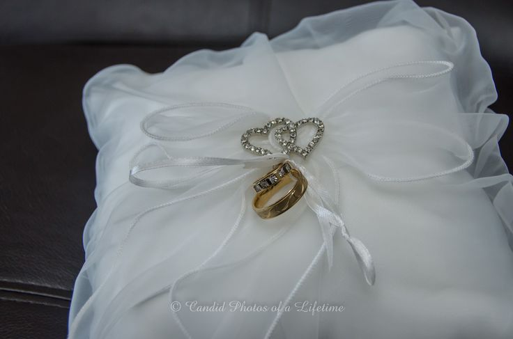 Wedding photographer, Candid Photos of a Lifetime  The wedding rings tied onto the ring pillow