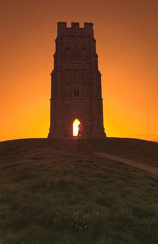 Glastonbury Tor is a hill at Glastonbury in the English county of Somerset, topped by the roofless St Michael's Tower which is a Grade I listed building. The whole site is managed by the National Trust and has been designated as a Scheduled monument. Artifacts from human visitation have been found dating from the Iron Age to Roman eras. The Tor is mentioned in Celtic mythology, particularly in myths linked to King Arthur.
