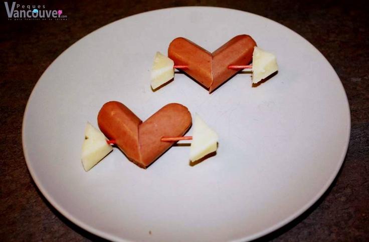 Salchichas corazón  Ingredientes:  • Un paquete de salchichas • Palillos • Un trozo de queso  Preparación: 1. Corta una salchicha a la mitad de manera diagonal. 2. Une las dos partes de la salchicha con un palillo. 3. Corta dos pedazos de queso uno en forma de la cabeza de la flecha y otro de la parte trasera.