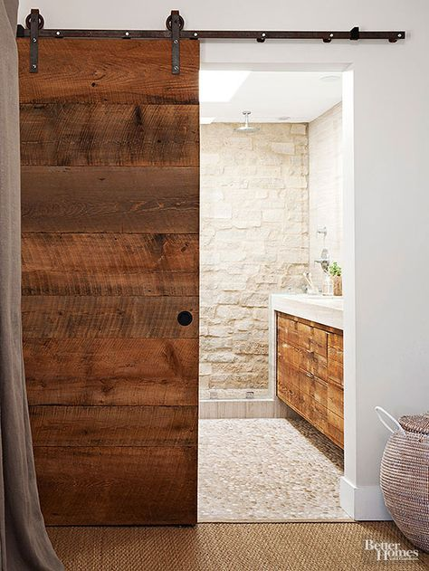 When used thoughtfully, all sorts of organic surfaces can unite to create pleasingly cohesive designs. Reclaimed boards craft an eye-catching barn door that slides open to reveal a ruggedly outfitted bathroom featuring stacked-stone walls and a river-rock floor. The raw wood reappears on a modern floating vanity inset in a sleek stone surround./