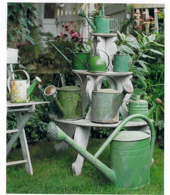 so love these old green watering cans on wooden plant stand....
