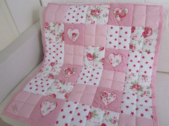 A traditionally made Patchwork Cot quilt with appliqued Hearts - 33 1/2 - 39 1/2 (85cm x 100cm) - 100% cotton fabrics - HAND QUILTED AND HAND FINISHED.  The Quilt has 4oz polyester wadding.  All the quilts are listed elsewhere, they will from time to time disappear before the listing has ended.  Machine washable on 30 degrees gentle/wool wash - dry flat.