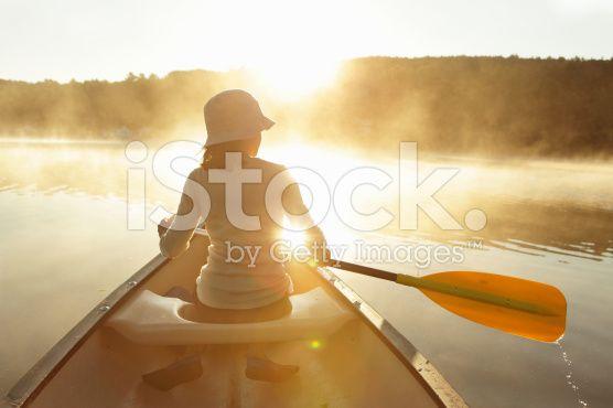 Outdoors girl paddling canoe on lake in bright misty sunrise – lizenzfreie Stock-Fotografie