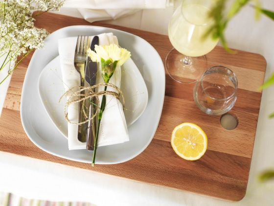 White tableware arranged on a wooden chopping board, complemented by natural touches like freshly cut wildflowers and lemons makes an enticing table setting.