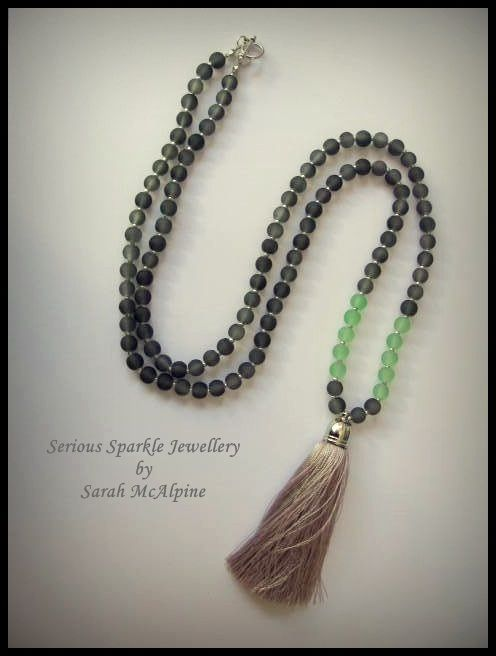 This stunning necklace is handmade from gorgeous gery frosted glass beads with tiny silver glass bead spacers and mint frosted glass bead accents. At the end hangs a luscious, soft grey silk tassel hanging from a silver cap.    The necklace fastens with a silver toggle clasp and measures 8cm in length. The tassel is 8cm long.