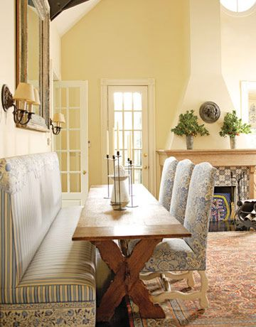 A Frenchy Pierre Frey print and a related border are wonderful with a Cowtan & Tout stripe on a banquette and chairs in this sunny breakfast area with a working woodburning fireplace. The antique refectory table is from Atelier Branca.