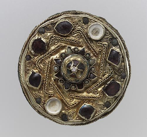 Disk Brooch, 675–700  Frankish; Found in Niederbreisig, western Germany  Gold sheet with filigree and inlays of garnet, glass, and mother-of-pearl