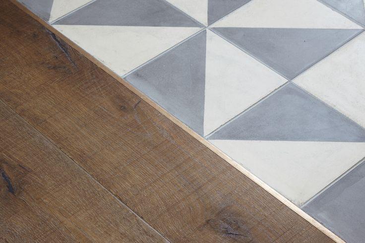 Piastrelle di cemento encausto bicromatiche e parquet di quercia.