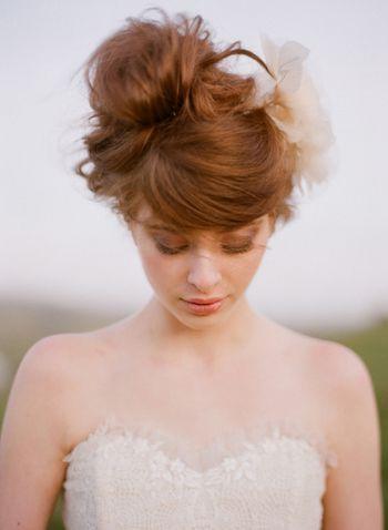 """ウェディングドレスに""""トップノット""""ヘアーが新鮮。あえてスッキリとまとめ過ぎず緩やかな髪の流れをつくるのが、現代的なお団子ヘアに仕上がる鍵です。"""