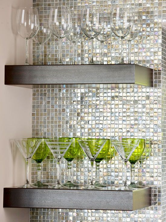 """Have a tiny bite of unused wall? BHG suggests turning the space into """"Newfound Storage"""". Floating shelves installed on a wall of metallic mosaics creates a beautiful display area for stem or glassware. In a small space, you want to make sure that you don't overwhelm your """"little bite"""" of wall with big bulky items. Keep the items as """"see-through"""" as possible to eliminate visual clutter."""